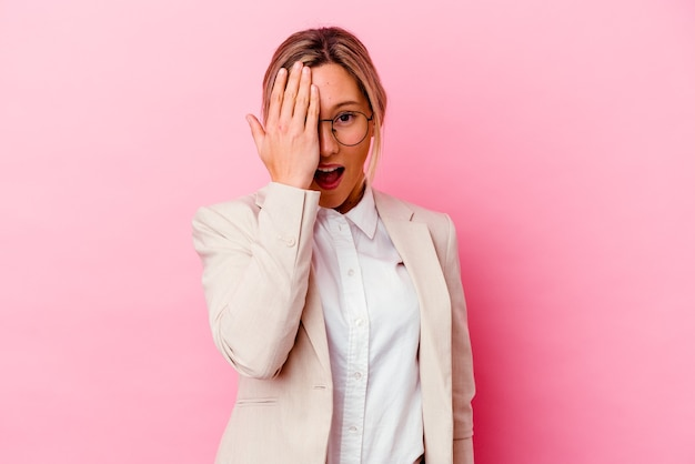 손바닥으로 얼굴의 절반을 덮고 재미 분홍색 벽에 고립 된 젊은 백인 혼혈 비즈니스 여자.
