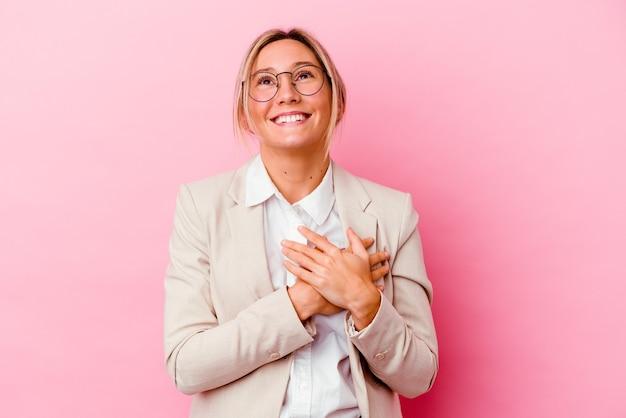 젊은 백인 혼혈 비즈니스 여자 마음, 행복의 개념에 유지 손을 웃 고 분홍색 벽에 고립.