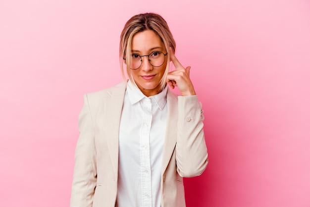 생각, 작업에 초점을 맞춘 손가락으로 사원을 가리키는 분홍색 벽에 고립 된 젊은 백인 혼혈 비즈니스 여자.