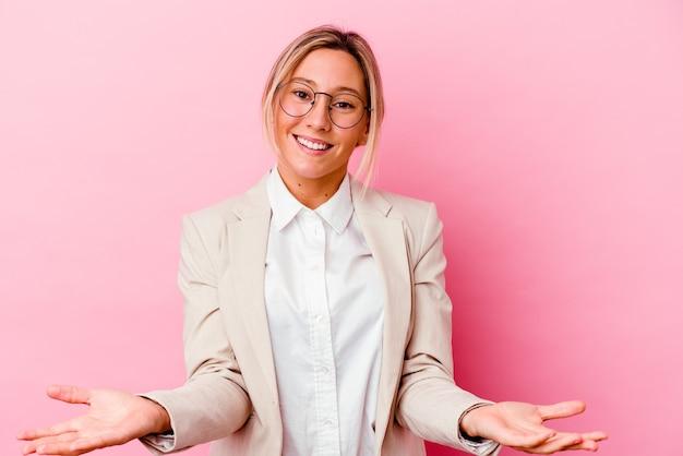 친절 한 표정을 보여주는 분홍색 벽에 고립 된 젊은 백인 혼혈 비즈니스 여자.