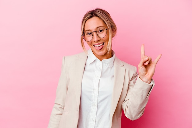 Young caucasian mixed race business woman isolated on pink background showing a horns gesture as a revolution concept.
