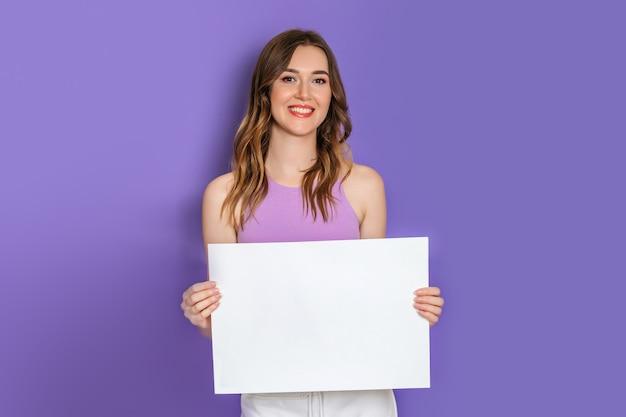 ライラックの背景に分離された笑顔の手に白い正方形の紙を保持している若い白人モデル。コピースペース