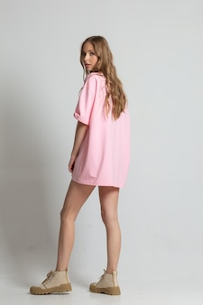 白いスタジオのサイクロラマでカメラにポーズをとってピンクのtシャツを着た若い白人モデル