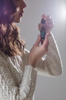 La giovane modella caucasica con lunghi capelli scuri posa per la telecamera con la mano vicino al viso