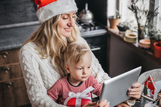 彼女の幼い息子と新年のサンタの帽子をかぶった若い白人の母親 Premium写真