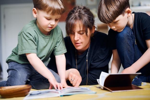 Молодая кавказская мать проводит время дома с сыновьями и читает книги на полу. счастливый родитель, играющий с детьми дошкольного возраста. концепция домашнего образования