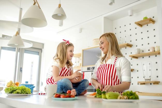 Молодая кавказская мать разговаривает со своей дочерью на прилавке в одинаковых фартуках на кухне