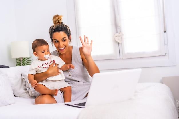 침대 재택 근무와 그녀의 아이를 돌보는 방에 그녀의 아들과 함께 젊은 백인 어머니