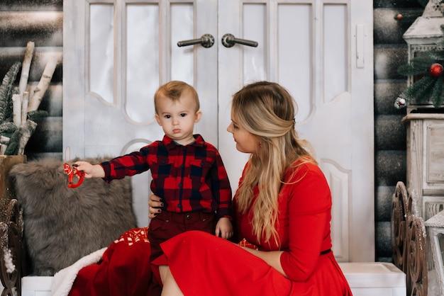 크리스마스 트리 근처 작은 아들과 함께 젊은 백인 어머니. 겨울 휴가를 축하하고 아기와 함께 연주의 개념.