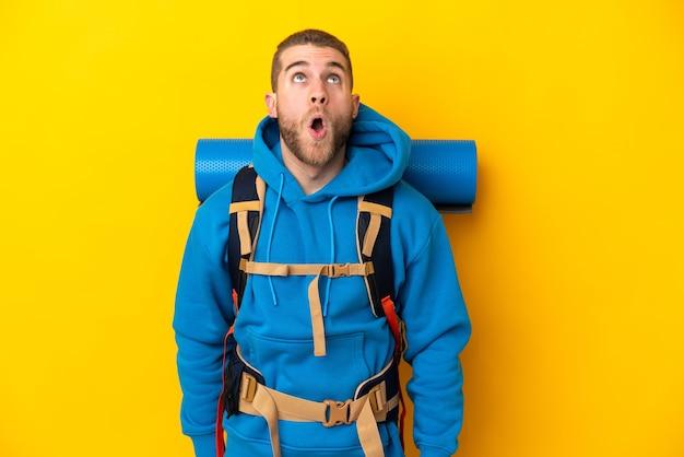 Молодой кавказский альпинист с большим рюкзаком на желтом фоне смотрит вверх и с удивленным выражением лица