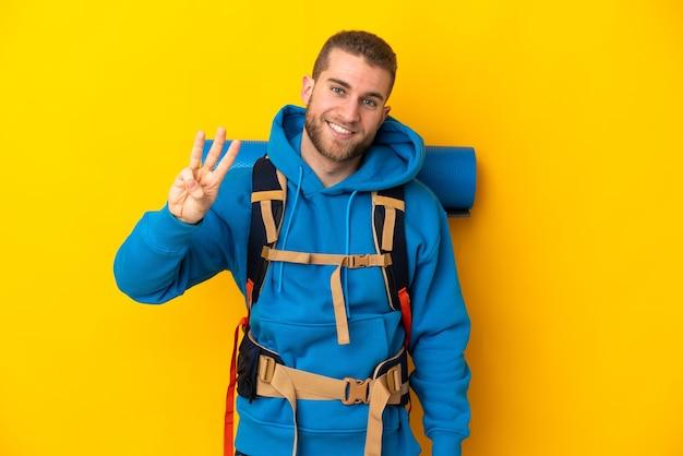 幸せで、指で3を数える黄色の壁に分離された大きなバックパックを持つ若い白人登山家の男