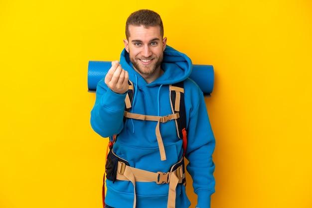 Молодой кавказский альпинист с большим рюкзаком изолирован на желтой стене делает денежный жест