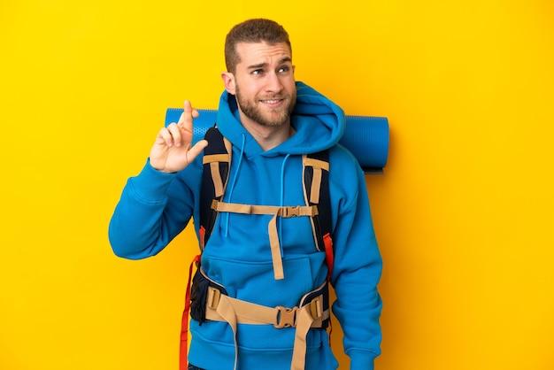 孤立した大きなバックパックを持つ若い白人登山家の男