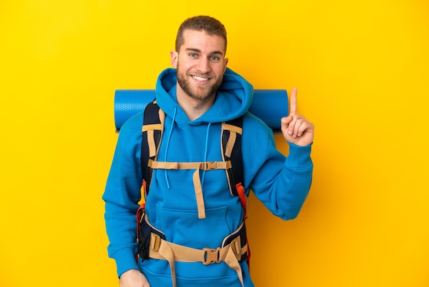 Young caucasian mountaineer man with a big backpack isolated on yellow background pointing up a great idea