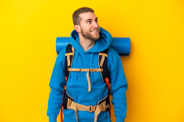 Young caucasian mountaineer man with a big backpack isolated on yellow thinking an idea while looking up
