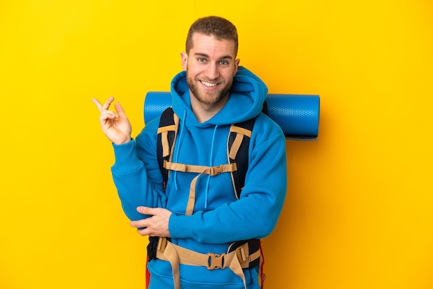 Young caucasian mountaineer man with a big backpack isolated
