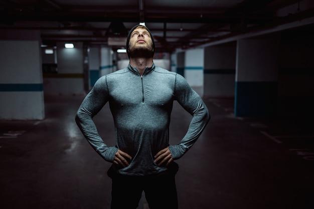 Молодой кавказский мускулистый спортсмен с шапочкой, стоя в гараже с руками на бедре поздно ночью