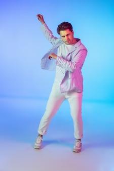 젊은 백인 음악가, 댄서, 파티 호스트, 네온 불빛의 그라데이션 배경 dj