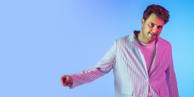 네온 불빛의 그라데이션 배경에서 젊은 백인 음악가 댄서 파티 호스트 dj