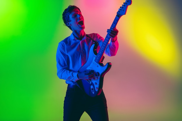 Young caucasian musician, guitarist playing on gradient space in neon light. concept of music, hobby, festival