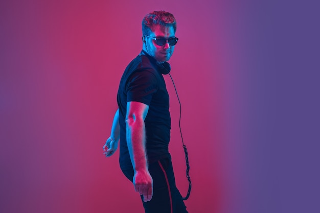 Young caucasian musician in headphones singing on gradient pink-purple wall in neon light. concept of music, hobby, festival. joyful party host, dj, stand upper. colorful portrait of artist.
