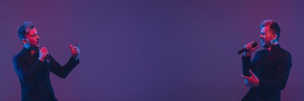 Молодой кавказский музыкант в случайных танцах на градиентном фиолетовом фоне в неоновом свете. понятие музыки, хобби, фестиваля. радостный хозяин вечеринки, ди-джей, трибунал, танцор. флаер с copyspace.