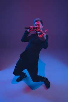 Young caucasian musician, performer singing, dancing in neon light on gradient background