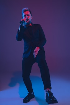 Young caucasian musician performer singing dancing in neon light on gradient background