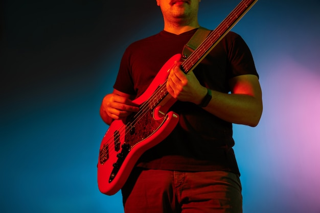 Young caucasian musician playing on gradient background in neon light.