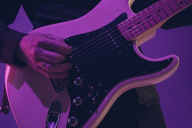 Young caucasian musician playing guitar in neon light on purple