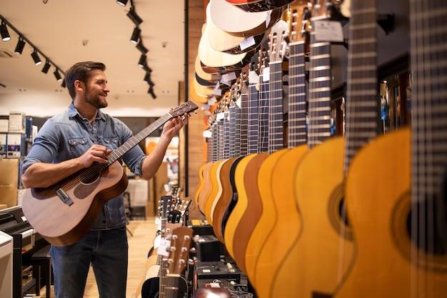 Молодой кавказский музыкант тестирует и играет на новой гитаре в музыкальном магазине.