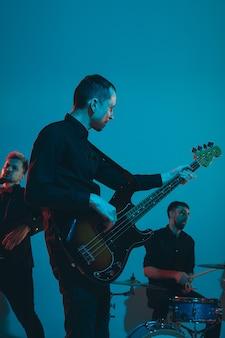 파란색 스튜디오 배경에서 네온 불빛으로 공연하는 젊은 백인 음악가 밴드