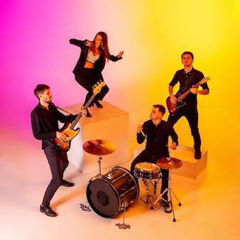 젊은 백인 음악가, 그라데이션 스튜디오 배경에서 네온 불빛으로 공연하는 밴드