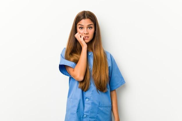 神経質で非常に心配な爪を噛む若い白人看護師女性。
