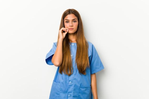 Молодая кавказская женщина медсестры с пальцами на губах держа секрет.