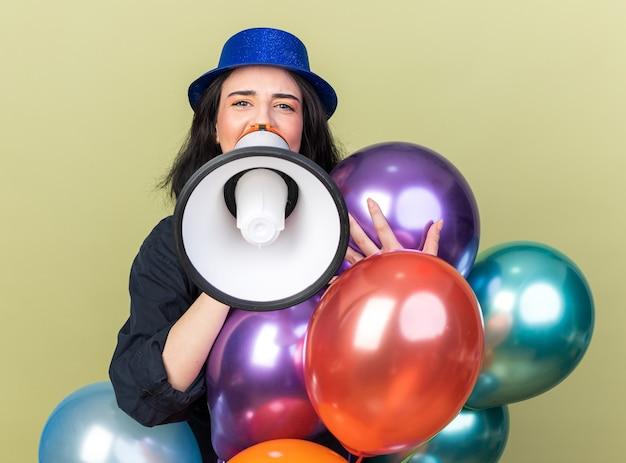 Giovane ragazza caucasica che indossa un cappello da festa in piedi dietro palloncini che gridano in un altoparlante isolato su una parete verde oliva