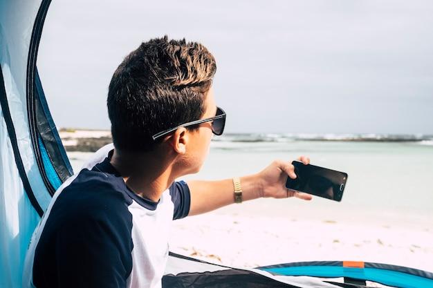 現代の技術デバイスの電話で写真を撮って後ろから見た若い白人のハンサムな男の子-旅行とキャンプのコンセプト-