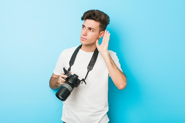가십을 듣고하려고 카메라를 들고 젊은 백인 사진 작가 남자.