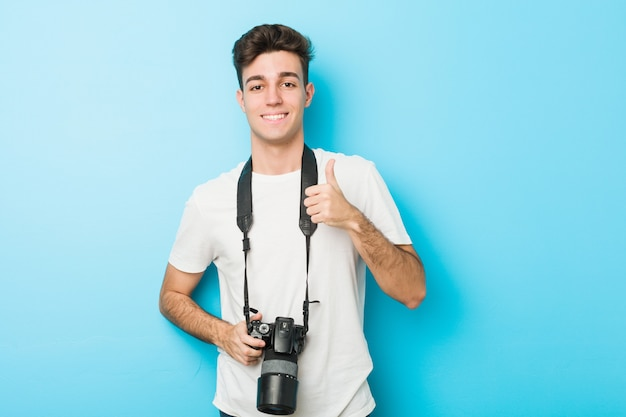 Young caucasian photographer man holding  smiling and raising thumb up