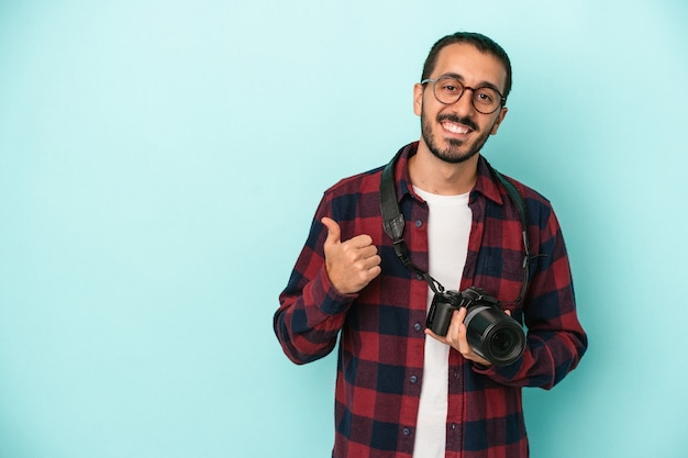 Young caucasian photographer man isolated on blue background smiling and raising thumb up