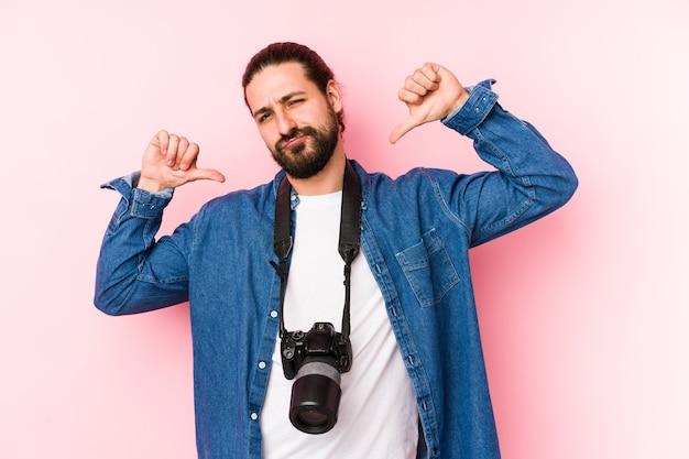 고립 된 젊은 백인 사진 작가 남자는 자부심과 자신감을 느낍니다.