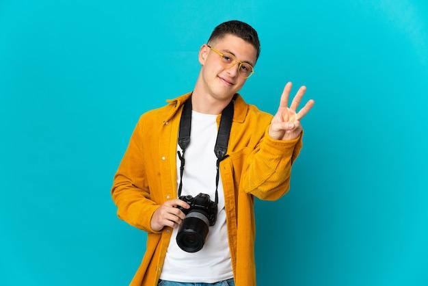 幸せな青で隔離され、指で3を数える若い白人写真家の男