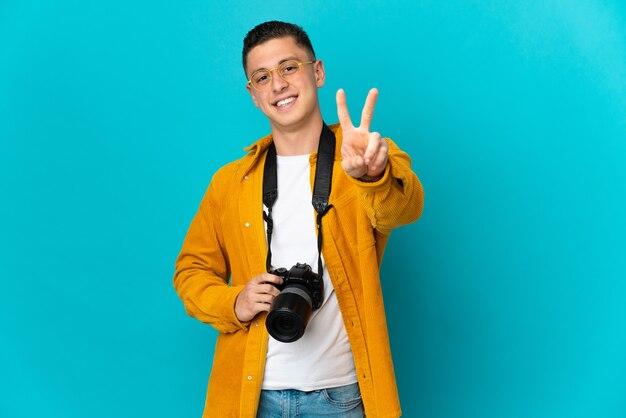 Молодой кавказский фотограф человек изолирован на синем, улыбаясь и показывая знак победы