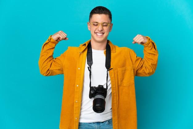 Молодой кавказский фотограф человек изолирован на синей стене делает сильный жест