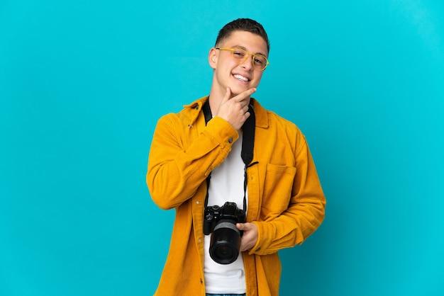 Молодой кавказский фотограф человек изолирован на синей стене счастливым и улыбается