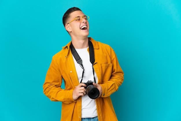 Молодой кавказский фотограф человек изолирован на синей стене смеется