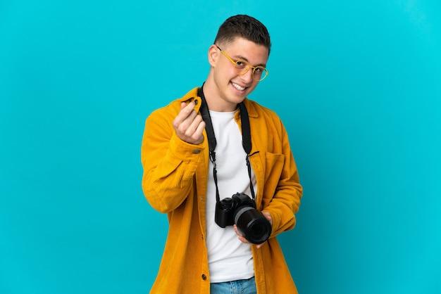 Молодой кавказский фотограф человек изолирован на синей стене делает денежный жест