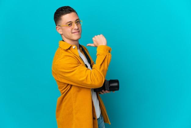 Молодой кавказский фотограф человек изолирован на синей стене, гордый и самодовольный