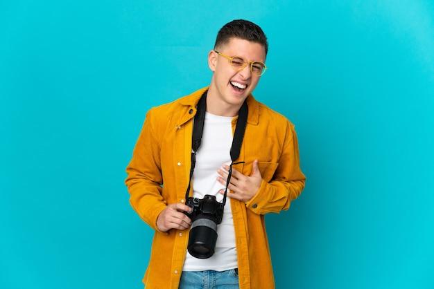 Молодой кавказский фотограф человек изолирован на синей стене, много улыбаясь