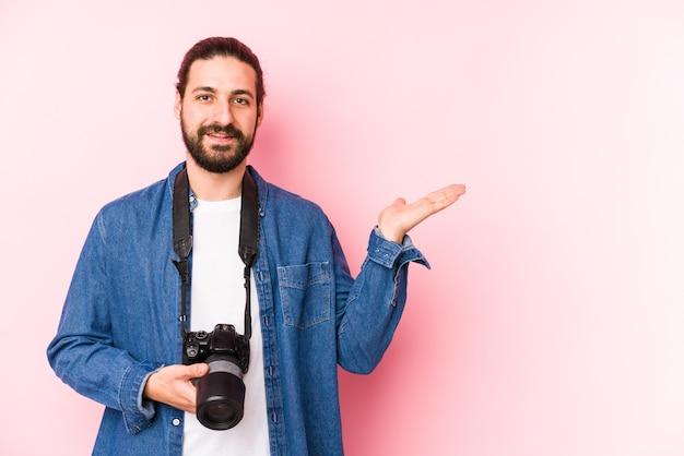 젊은 백인 사진 작가 남자 손바닥에 복사본 공간을 표시 하 고 허리에 다른 손을 잡고 격리.
